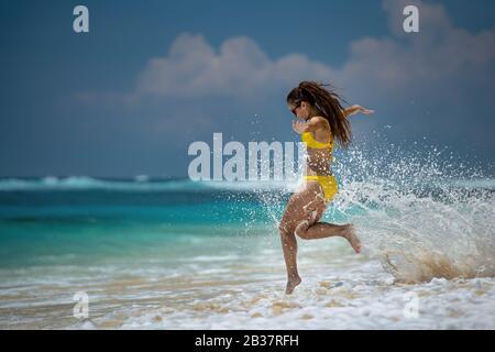 Feliz delgado hermosa chica vestida con traje de baño amarillo corre y salta en las olas del mar. Concepto de vacaciones en el mar