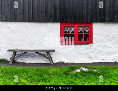 Pared blanca de la casa con ventana roja en la antigua casa faroesa. Banco de madera sobre hierba verde. Islas Feroe, Dinamarca