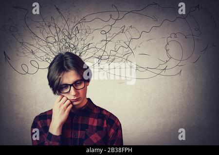 Retrato de primer plano de un adolescente triste y reflexivo, mano bajo la mejilla, mirando hacia abajo sentir dolor de cabeza, aislado en la pared gris. Niño disgustado que experimenta adolescente