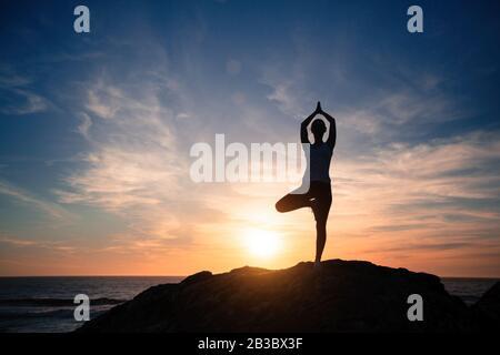Silueta de una mujer de yoga haciendo ejercicios en la playa del mar durante la puesta de sol increíble.