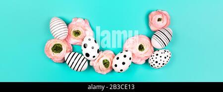 Gráfico creativo huevos pintados a mano y ranunculus flores sobre fondo azul pastel. Concepto de Pascua. Lugar para el texto.