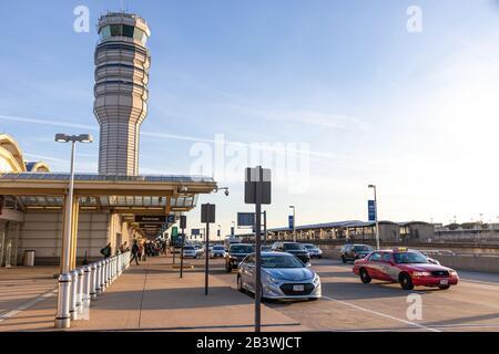 Ronald Reagan Washington National Airport Terminal B/C en la ajetreada y soleada tarde con la Torre de Control de tráfico aéreo vista al fondo.