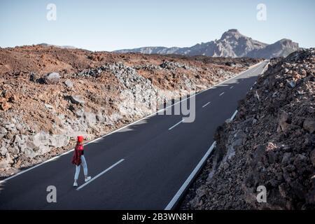 Vista del paisaje en el valle volcánico con pintoresco camino recto y mujer caminando en él durante un día soleado. Viajando por la isla de Tenerife, España