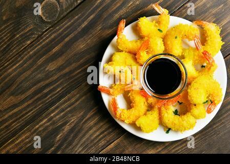 Camarón empanado frito con salsa sobre plato sobre fondo de madera con espacio libre. Vista superior, disposición plana