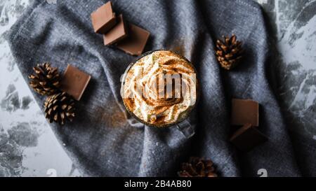 Café helado con crema sobre mesa rústica, bebida de café en una taza transparente con chocolate