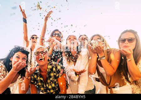 Gente que se divierte en fiesta celebración amigos concepto - grupo de mujeres jóvenes y adultos todos juntos riendo soplando confeti de color - amistad y amor por el estilo de vida con las generaciones activas mixtas