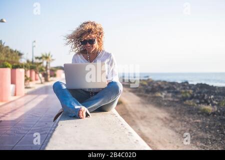 Alegre hermosa rubia rizado gente joven mujer adulta sentada al aire libre con el mar y el cielo en el fondo trabajando con la tableta ordenador conectado a Internet - la libertad de la oficina concepto Foto de stock