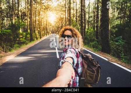 Pareja viajeros Hombre y Mujer seguir sosteniendo las manos en el camino largo paisaje forestal y el sol en el fondo Amor y viaje emociones felices estilo de vida concepto. Personas que viajan vacaciones activas de aventura
