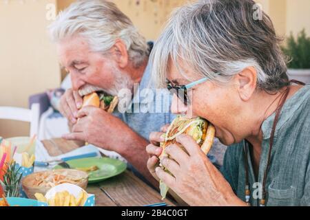 Gente comiendo comida basura de la hamburguesas - Pareja del hombre mayor y de la mujer con comida rápida a la hora del almuerzo - cerca de los ancianos sin un estilo de vida saludable - sabroso sándwich lleno de todo