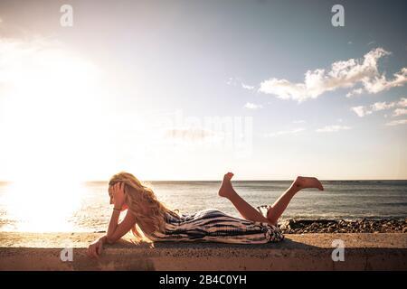 Hermosa larga rubia cabello joven tumbarse y disfrutar de la puesta de sol en el mar - chica independiente con el océano y la luz del sol puesta de sol en el fondo - disfrutar de la libertad y vacaciones de verano