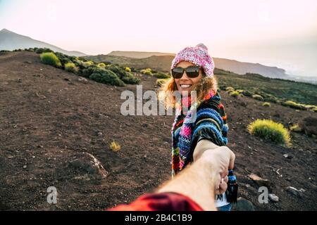 Hermosa mujer joven adulto alegre sonrisa y la mano de hombre durante el ocio al aire libre actividad trekking en la montaña - viaje concepto de pareja para la gente activa - libertad vacaciones en la naturaleza
