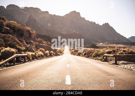 Hermoso y pintoresco camino largo con enfoque en primer plano - efecto de desenfoque de fondo y destino de viaje con efecto sunilght y montañas