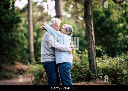Pareja activa mayor disfrutando del bosque natural al aire libre con hugs y amor juntos - concepto de vida para siempre con hombre y mujer maduro - ancianos y hermoso bosque verde en el fondo