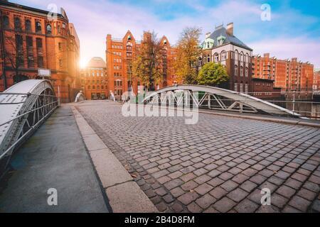 Puente sobre canales con calle adoquinada en el distrito de almacenes de Hamburgo, Alemania, Europa, edificio histórico de ladrillo iluminado por la puesta de sol dorada