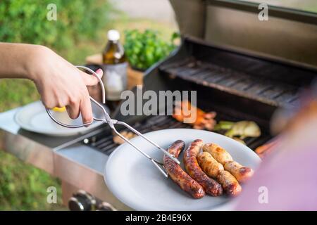 Se sirven salchichas a la parrilla en un plato y barbacoa