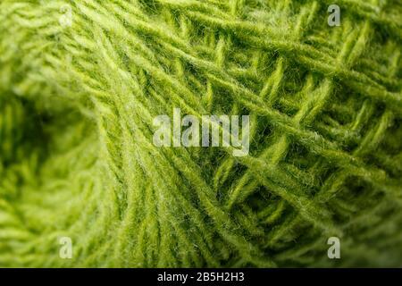 Hilados de lana cierran hilos verdes de colores para el trabajo de agujas en macro. Tejido de textura de fondo para la aguja de punto. Hilo de lana de pantalla completa.