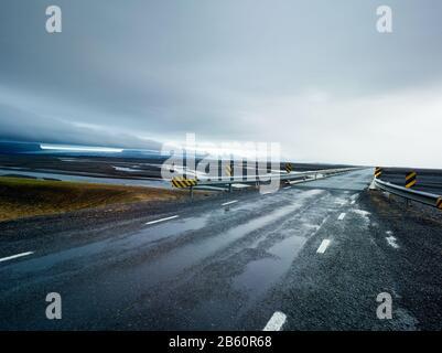 Carretera de campo con un puente de acero sobre un paisaje volcánico en un día nublado y lluvioso en Islandia