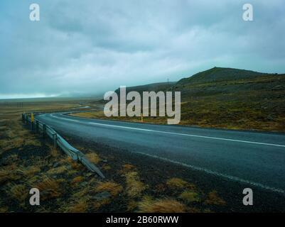 Carretera con barreras de impacto en un día nublado y lluvioso en Islandia