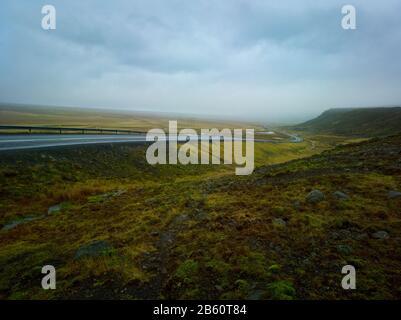 Sinuosa carretera rural en un día nublado y lluvioso en Islandia