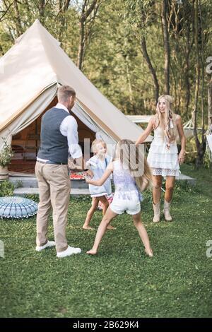 La familia joven está jugando juntos en un día soleado en el parque. Padre, madre y dos hijas en ropa boho casual bailando y saltando, sosteniendo las manos adentro