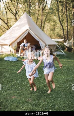 Hermosa familia joven pasar tiempo juntos en el parque de verano o pradera, teniendo un picnic. Padres jóvenes sentados cerca de wigwam, mientras que dos niñas