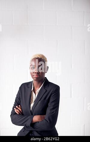 Retrato De Una Joven Empresaria Determinada Que Lleva El Traje De Pie Contra La Pared Blanca Del Estudio