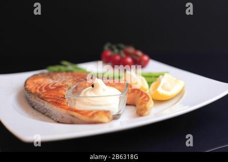 filetes de salmón con verduras y especias: espárragos, tomates, jengibre, pimentones, sal, chile, cebolla, limón y aceite de oliva sobre fondo negro. Sane