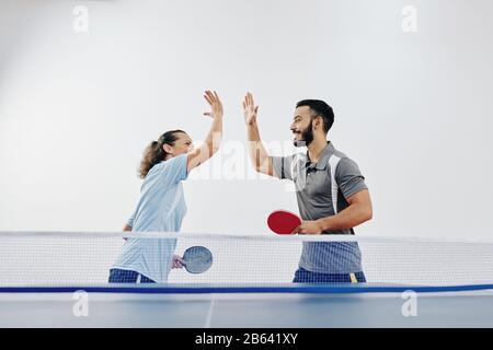 Feliz equipo de jugadores de tenis que se dan unos a otros cinco altos después de ganar el juego en la competición