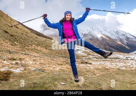 una mujer joven feliz mientras que el senderismo en las altas montañas levantó sus postes del trekking
