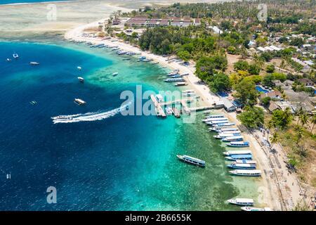 Vista aérea de barcos amarrados en un hermoso arrecife de coral tropical y la playa en una pequeña isla (Gili Air, Indonesia)