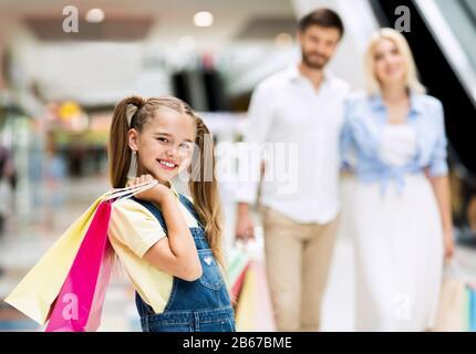 Hija Sosteniendo Bolsas Caminando Con Los Padres Entre Las Tiendas En El Centro Comercial