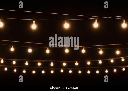 Guirnaldas de luces sobre un soporte de madera en la calle. Un banquete de bodas.