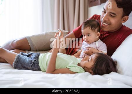 padre y sus dos hijas yacían en la cama mientras miraban el vídeo con un smartphone