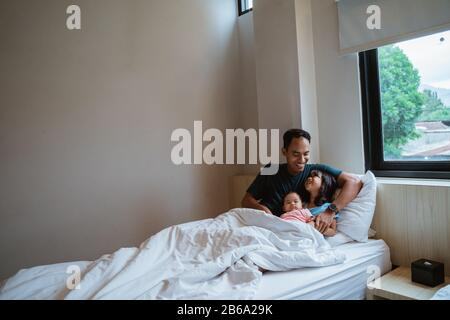 dos hijas y su padre se sientan en la cama cuando se despiertan