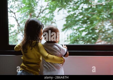 tres niños pequeños mirando por la ventana cuando están de pie en el dormitorio