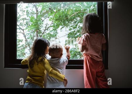 tres niños pequeños asiáticos viendo por el cristal de la ventana cuando están de pie en el dormitorio