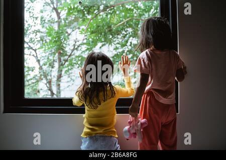 dos niños pequeños mirando por la ventana cuando están de pie en el dormitorio