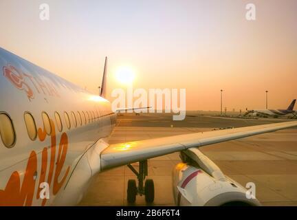 Bangkok, TAILANDIA-FEBRERO 20, 2020 : Thai Smile Airways. Avión de pasajeros estacionado en el aeropuerto de Suvarnabhumi. Ala de avión de primer plano con el cielo dorado del amanecer