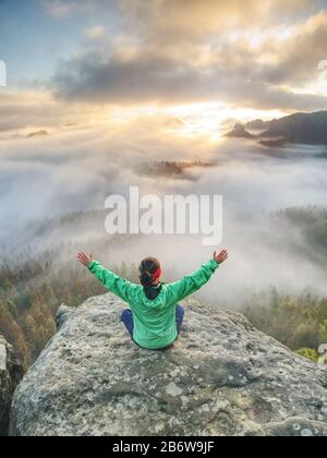 Feliz mujer sentada, brazos levantados por encima de la cabeza y celebrar la vida. Chica en pose de yoga. A la niña le encanta viajar. Vista desde la parte posterior del turista o