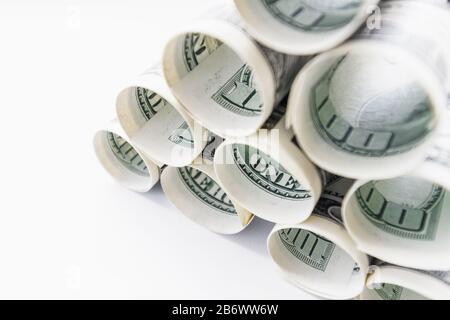 Billetes americanos de cien dólares rodados y apilados en una pirámide. Fondo claro, primer plano, enfoque selectivo