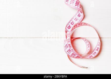 Vista superior de la cinta de medir, doblada en una espiral con espacio de copia. Concepto de accesorios de costura o dieta saludable sobre fondo de madera.