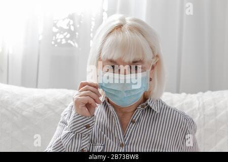 Una mujer rubia adulta en máscara médica se sienta en el sofá de la habitación. Protección antivirus, coronavirus, concepto ARVI