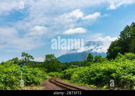 Hakodate línea principal de ferrocarril en la ciudad de Niseko en primavera soleado día con el Monte Yotei en el fondo. Subprefectura de Shiribeshi, Hokkaido, Japón