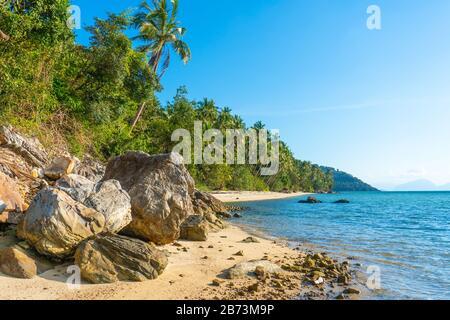 Playa de arena de una isla tropical paradisíaca y desierta. Palmeras que sobresalen en la playa. Arena blanca. Agua azul del océano. Descanse lejos de la gente.