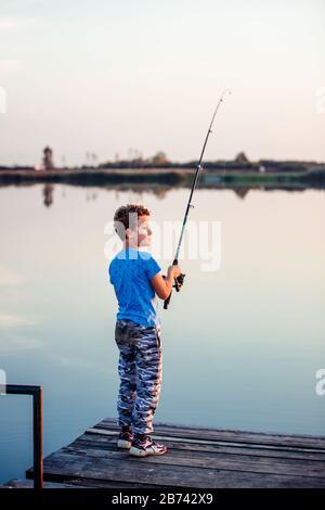 Un niño feliz con una caña de pescar. Lindo niño pescando en un lago en un soleado día de verano.