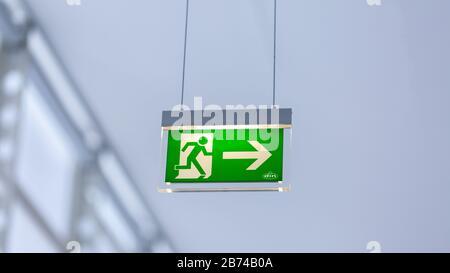 Vista de la señal de salida de emergencia iluminada. Con la figura y la flecha hacia la derecha. Fondo blanco neutro. Diseño moderno.