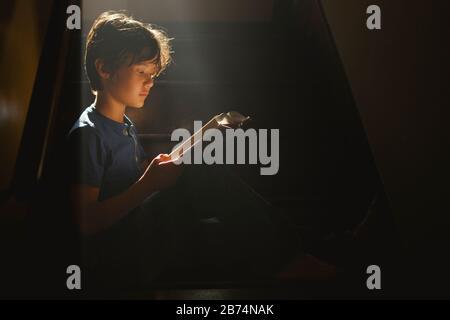 Un niño se sienta en una escalera oscura en un rayo de luz brillante de lectura