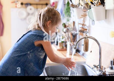 Los niños se lavan las manos en casa bajo el grifo. Niña en harina después de cocinar en la acogedora cocina casera.