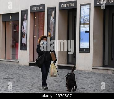 Berlín, Marzo De 12. 15 de marzo de 2020. Una mujer con una máscara de cara camina un perro en la calle comercial Via dei Condotti en Roma, Italia, el 12 de marzo de 2020. PARA IR CON LOS TITULARES DE XINHUA DEL 15 DE MARZO DE 2020. Crédito: Elisa Lingria/Xinhua/Alamy Live News