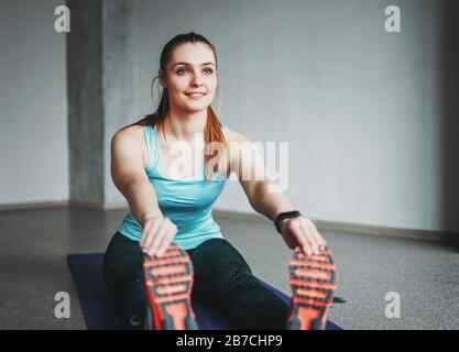 Atractivo ajuste joven mujer deporte ropa fitness chica modelo haciendo estiramientos en el estudio loft clase de entrenamiento